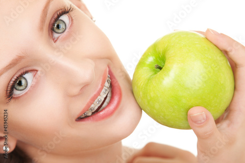 Fotografia  Cute girl in braces with green apple on white background