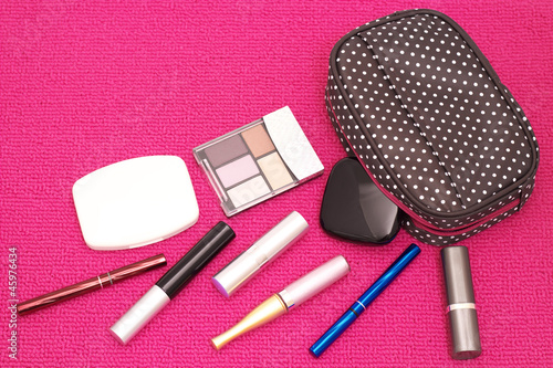Fotografie, Obraz  The scattered cosmetics with a cute pouch