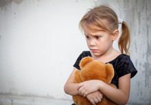 Sad Little Girl On Background The Wall