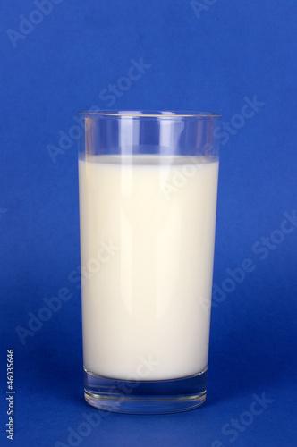 Glass of fresh new milk on blue background