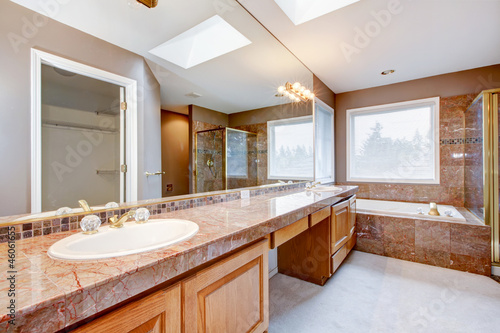Fotografía  Large luxury bathroom with red granite countertops and tub.