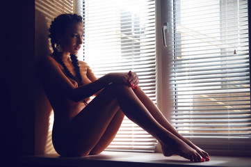 beautiful naked young woman on the window