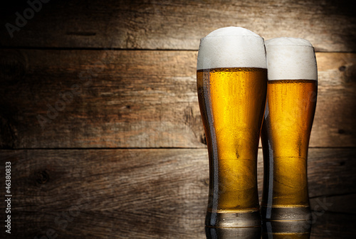 Two glass beer on wood background with copyspace Poster