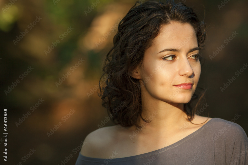 Valokuva  Young brunette woman with natural makeup and curly hair