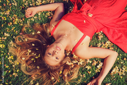 Fotografie, Obraz  Beautiful Young Woman Lying in Flowers