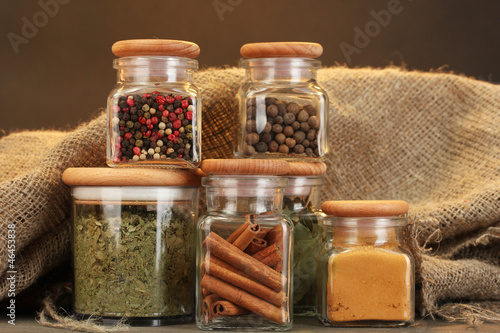 Photo Stands Herbs 2 jars with spices on wooden table on brown background