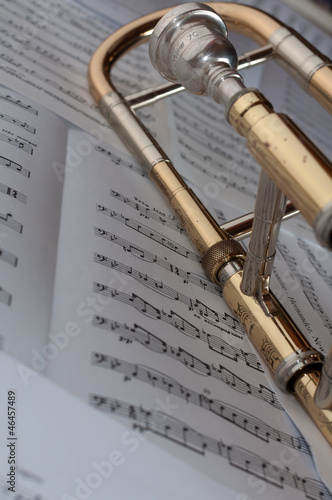 A trombone resting on a background of music Canvas Print