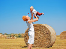 Young Woman And Little Son On The Field With Big Hay Bale Rolls