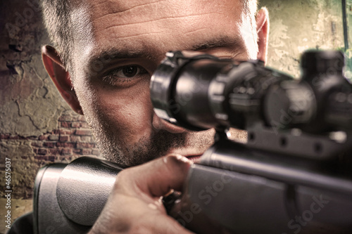 Photo  Portrait of serious man aiming with gun