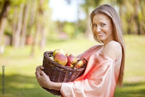Uśmiechnięta kobieta z koszem jabłek - fototapety na wymiar