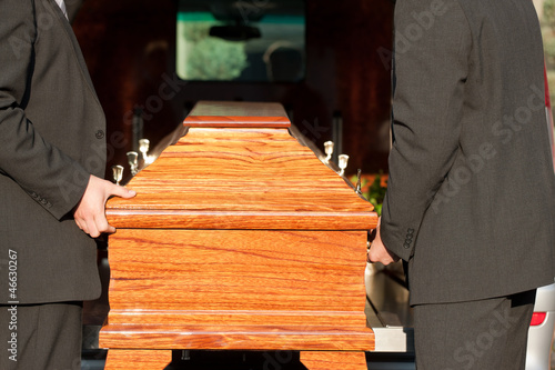 Photo  Funeral with casket carried by coffin bearer