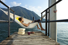 Portrait Of Young Man On Hammock Of Lake
