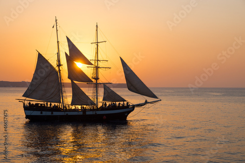 Foto op Canvas Schip A sailing ship at sunset