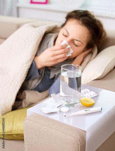 Fotografia  Sick Woman. Flu. Woman Caught Cold. Sneezing into Tissue