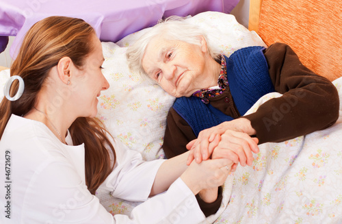 Fotografie, Obraz  Young doctor holds the elderly woman hands