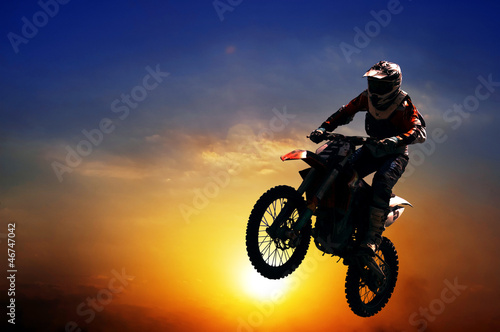 Silhouette of a motorcyclist on a background of dark sky