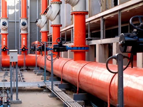 Fotografie, Obraz  valves and orange steel pipes at cooling tower