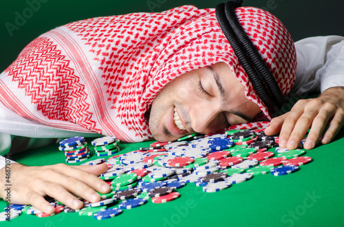 Arab playing in casino - gambling concept with man плакат