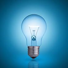 Light Bulb On Blue Background.