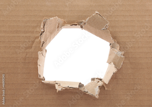 Fotografía  Ripped hole in cardboard on white background
