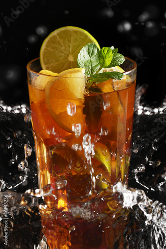 Foto op Canvas Opspattend water Fresh cold tea with lemon and mint in water splashing