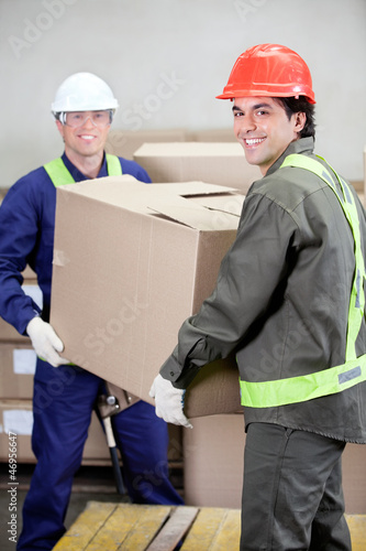Fotografie, Obraz  Foremen Lifting Cardboard Box in Warehouse