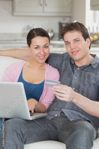 Two people using the laptop on the couch