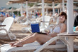 woman with laptop at resort beach