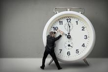 Businessman Pulling A Clock Ha...