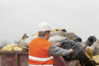 Worker with garbage and debris bags to a container