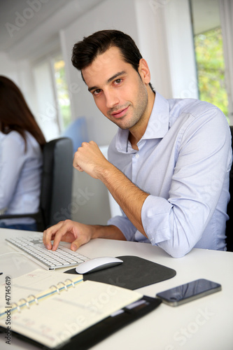 Garden Poster Portrait of young office worker sitting at desk