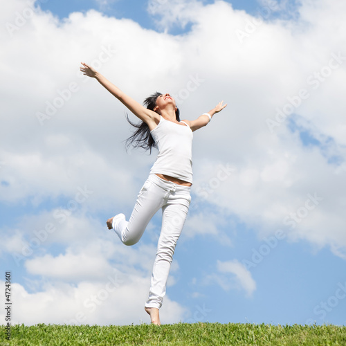 Photo  Pretty young woman jumping on green grass