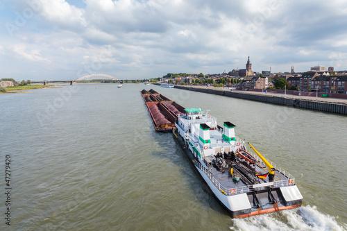 Fotografia  Cargo riverboat passing the Dutch city Nijmegen