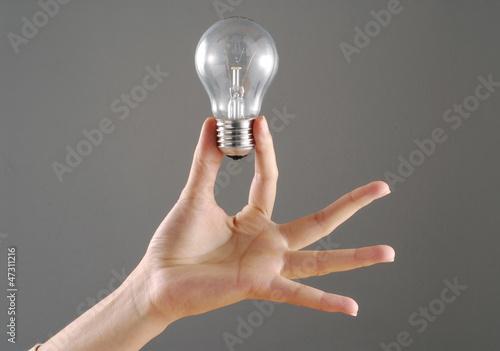 Fotografía  Mano femenina sujetando una bombilla,concepto de idea.