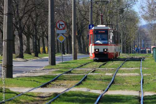 Red electric tram running through the damaged rails.