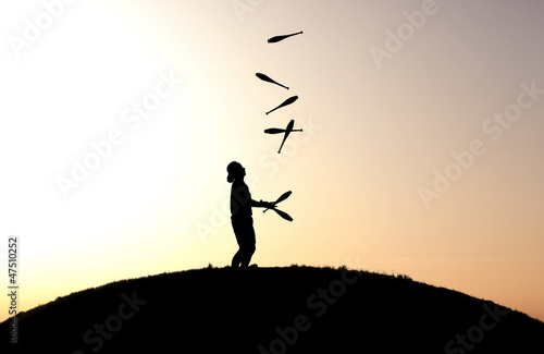 circus artist juggling with seven juggling clubs in sunset