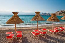 Sunshades And Orange Deck Chairs On Beach At Baska - Krk - Croat