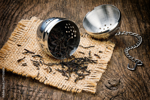 Fotografia, Obraz  Metal tea infuser on wooden table