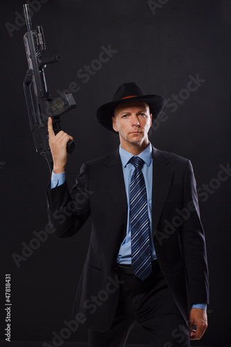 Photo  Serious man in a suit holding a rifle