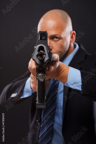 Serious man in a suit holding a rifle Wallpaper Mural