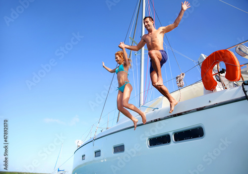 Fotografia  Young couple jumping in water from yacht