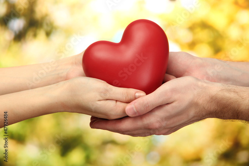 Fototapeta Red heart in woman and man hands, on green background