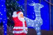 Leinwandbild Motiv Figures of Santa and deers with light bulbs inside under christm