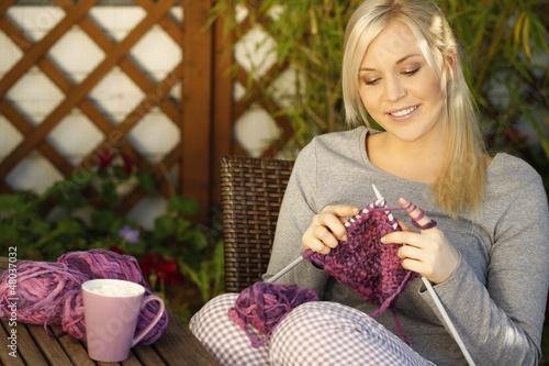 Fotografie, Obraz  Hübsche Frau mit Strickzeug auf der Terrasse