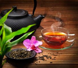 Fototapeta Arrangement aus Teekanne, Teeglas grünem Tee und Orchidee