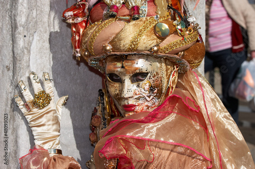 Person in Venetian costume attends Carnival of Venice.
