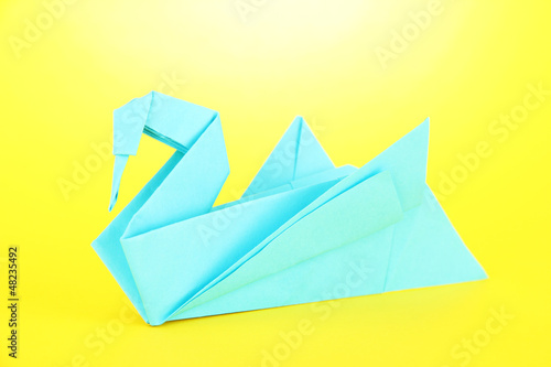 Origami swan on yellow background.