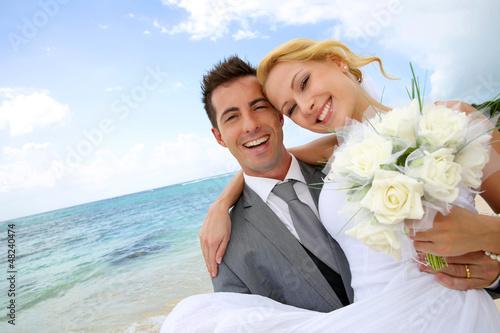 Fotografía  Groom holding bride in his arms at the beach