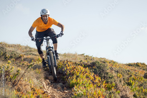 Mountain biker riding dirt trail Wallpaper Mural