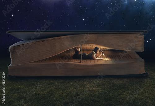 Fotografie, Obraz  Woman reading inside a huge book
